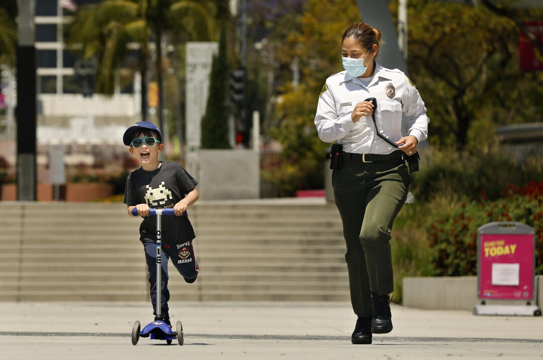Patton Soole, 5, left, shares a friendly race with L..A County Sheriff's Deputy Bridget Adams at Grand Park in downtown Los Angeles.