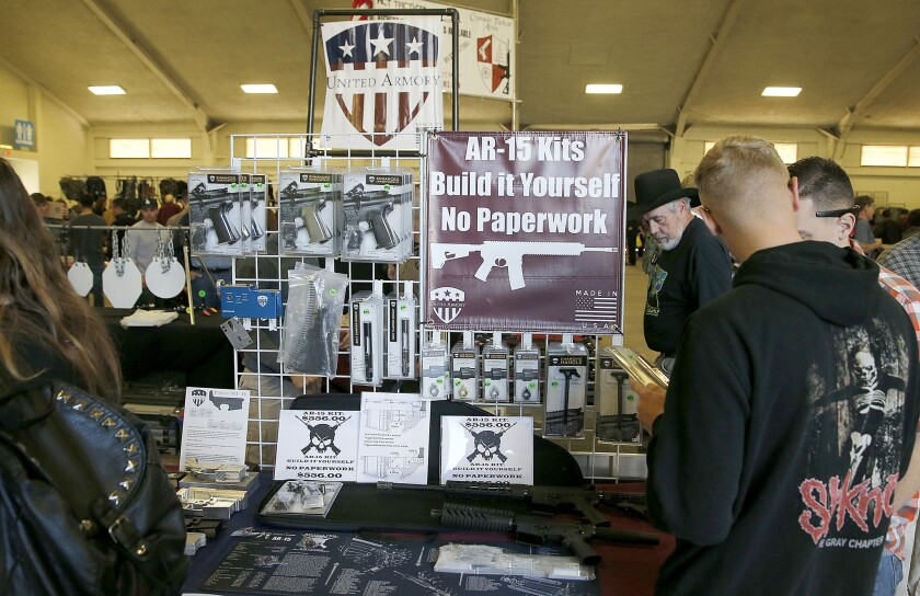 Gun enthusiasts view AR-15 semiautomatic assault rifle kits, which are legal in California, at a gun show last week in Del Mar.