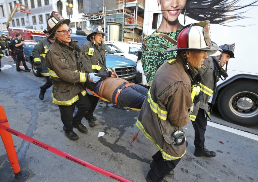 Firefighters tend to a passenger injured on an double-decker tour bus after it crashed into a construction site near Union Square in November 2015.