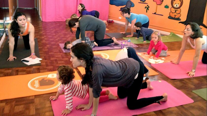 Mothers practice yoga with their young children. New research shows that when moms follow five healthy habits, their children are unlikely to become obese.