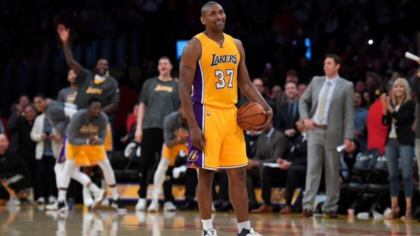 Los Angeles Lakers forward Metta World Peace stands on the court while teammates and fans cheer as t