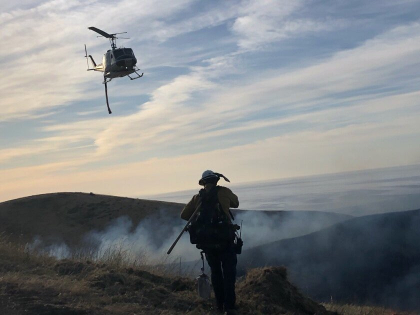 A firefighter battles a brush fire that broke out in the Hollister Ranch area of Santa Barbara County early Thursday.