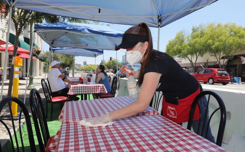 Filippi's Pizza manager Diana Gil uses disinfectant to clean a table and chairs in Escondido.