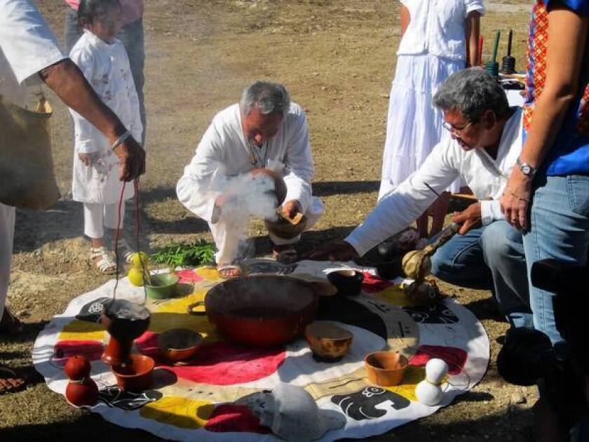 """Valerio Canche, center, president of a local association of Maya spiritual healers, presides over a """"Blessing of the Water"""" ceremony near Merida, Mexico. The city is hoping interest in the Maya calendar doomsday theories will prompt people to visit the region."""