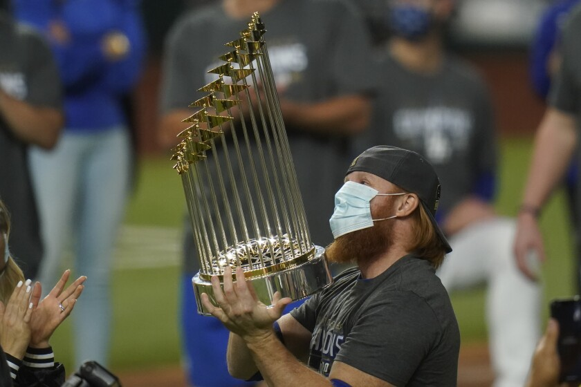 FILE - In this Tuesday, Oct. 27, 2020, file photo, Los Angeles Dodgers third baseman Justin Turner celebrates with the trophy after defeating the Tampa Bay Rays 3-1 to win the baseball World Series in Game 6 in Arlington, Texas. Baseball nearly made it through its version of playoff bubbles unscathed; two innings before the World Series ended, Justin Turner of the now-champion Los Angeles Dodgers Turner was pulled from the game after MLB was notified that he had tested positive for COVID-19. (AP Photo/Eric Gay, File)