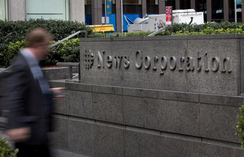 News Corp. reported lower revenue in the July-September quarter compared with 2012. In a file photo, a pedestrian walks past the News Corp. headquarters in New York in November 2012.