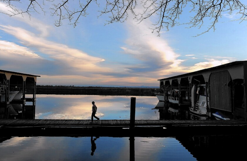 A woman walks on a dock in the delta near Stockton. The state's proposal calls for two enormous tunnels under the Sacramento-San Joaquin River Delta that would deliver water to Central Valley farmers, L.A. and other cities.