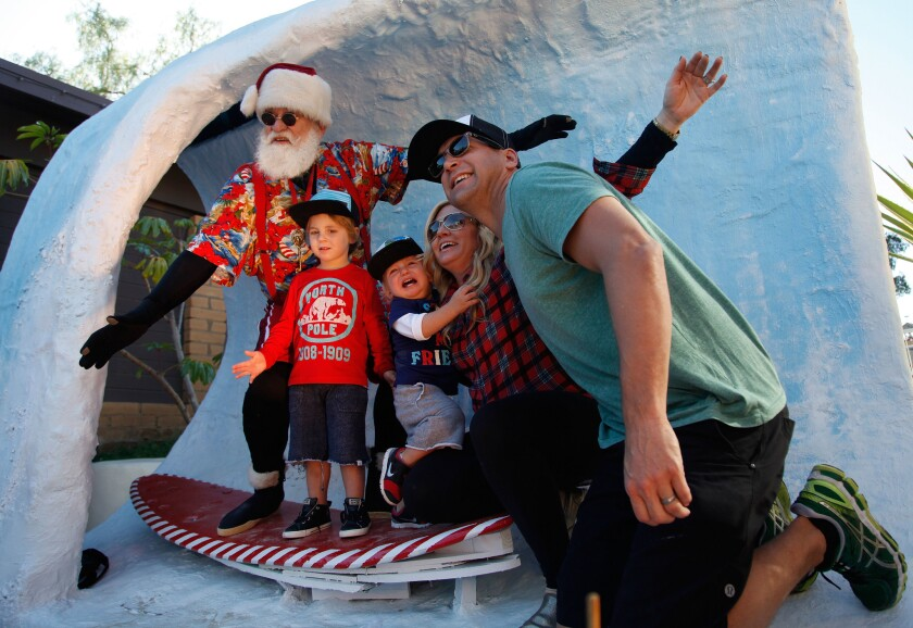The Dorf family (From left to right) Maxwell Dorf, 3, Jace Dorf, 1, Christina Dorf and Barron Dorf of San Diego pose for a photo with Surfin' Santa at Seaport Village Saturday.