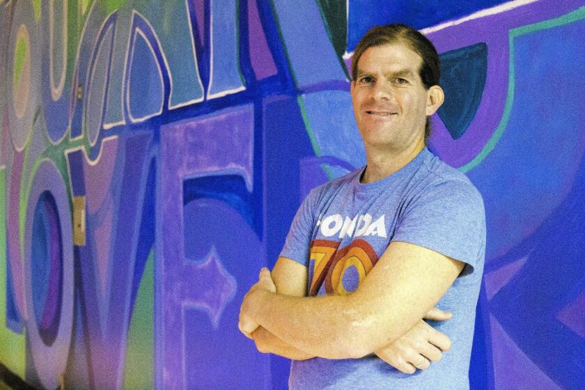 """Alex Cook, a Boston-based artist who started the """"You Are Loved"""" project in 2014, stands in front of his newest mural in the chapel of the Orange County Men's Jail in Santa Ana."""
