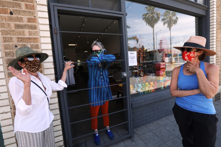 Holly Boies, center, talks with longtime shoppers Enid Koffler, left, and her daughter Samara Koffler on Friday at the entrance of Boies' store, Salt, on Abbott Kinney Boulevard in Venice.