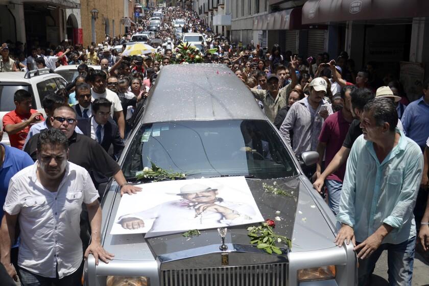 """Miles de personas participan en el funeral del cantautor mexicano Joan Sebastian en las calles de Cuernavaca, México, el míercoles 15 de julio de 2015. El músico ganador del Grammy y el Latin Grammy murió el lunes. Era famoso por canciones sentimentales como """"Tatuajes"""" y """"Secreto de Amor"""". Tenía 64 años. (Foto AP/Tony Rivera)"""