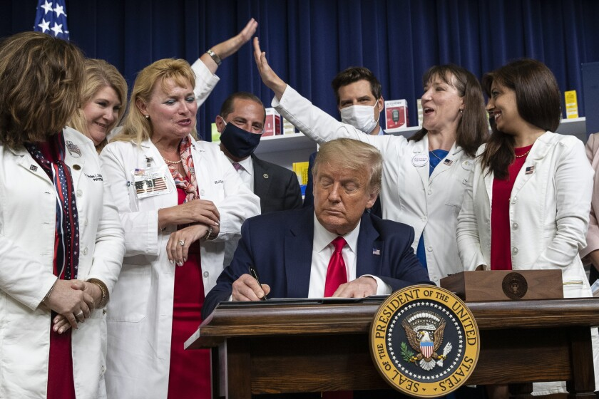 Supporters celebrate as President Trump signs an executive order on lowering drug prices on July 24.
