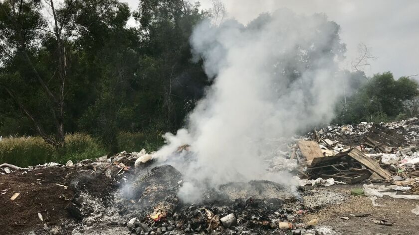 A fire burns at an illegal dumpsite in Port Klang, Malaysia.