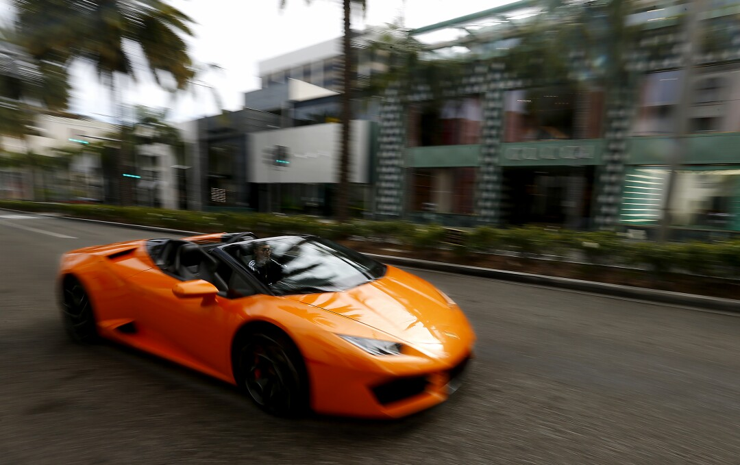 A young man drives a sports car down Rodeo Drive in Beverly Hills, where shops were closed and streets largely devoid of people and motor traffic.