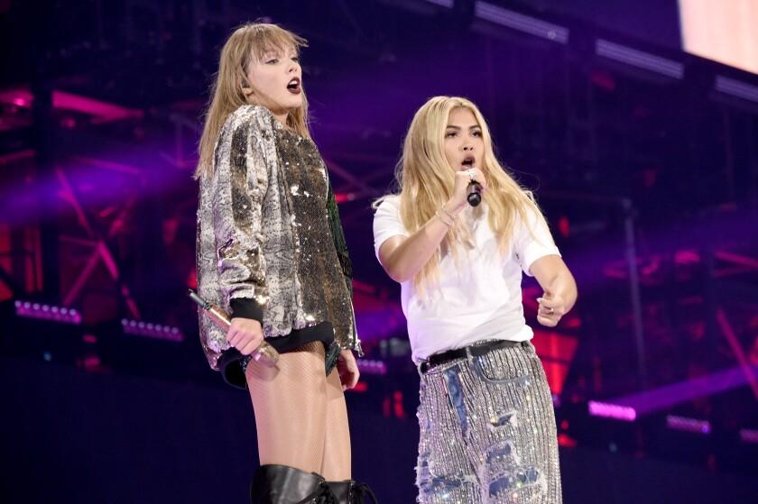 Taylor Swift, left, and Hayley Kiyoko onstage.