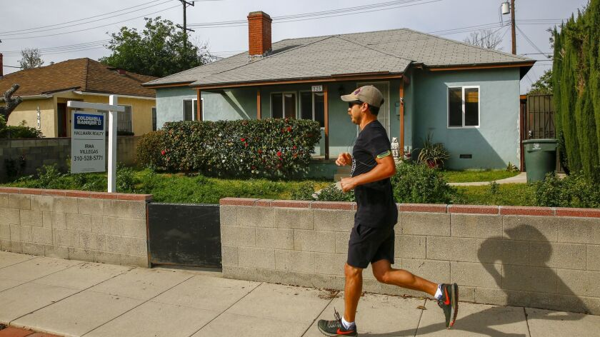 A runner runs jogs past a home for sale on Buena Vista Street in Burbank in March.