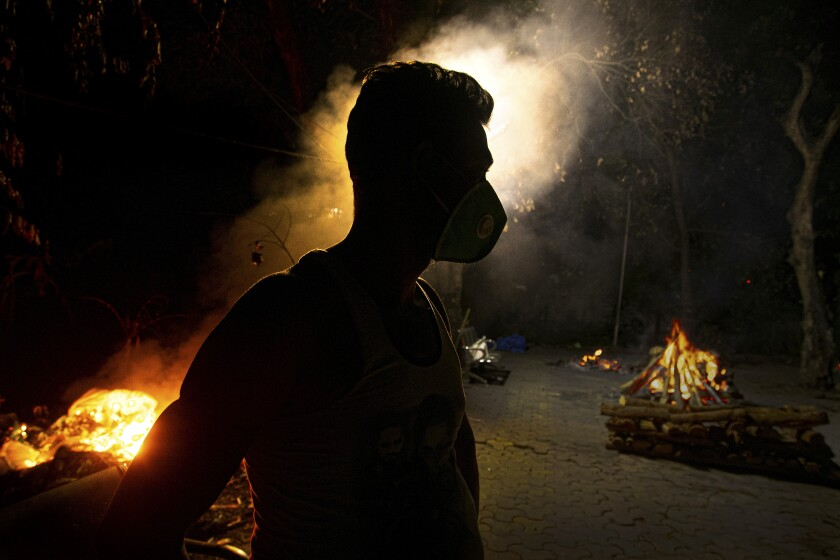Ramananda Sarkar, 43, stands by burning funeral pyres of COVID-19 victims in Gauhati, India, Monday, Sept. 14, 2020. Sarkar, who was deep in debt and desperate for money, took the job of lighting funeral pyres after failing to pay back a loan he'd taken to start selling sugarcane juice on a wooden cart. While Hindu's believe cremation rights are sacred and release the dead person's soul from the cycle of rebirth, those who actually deal with corpses are looked down upon. Sarkar said he alone has cremated more than 450 COVID-19 victims. (AP Photo/Anupam Nath)