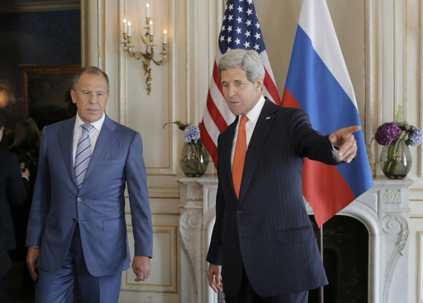 U.S. Secretary of State John Kerry, right, greets his Russian counterpart, Sergey Lavrov, prior to their meeting in Paris, France, Thursday, June 5, 2014. Diplomatic efforts to resolve the months-long standoff between Ukraine and Russia kicked into high gear in two European capitals on Thursday. (AP Photo/Laurent Cipriani, pool)