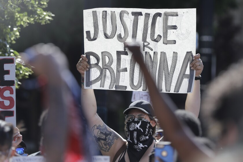 A protester holds a sign during a protest  in Louisville, Ky., over the deaths of George Floyd and Breonna Taylor.