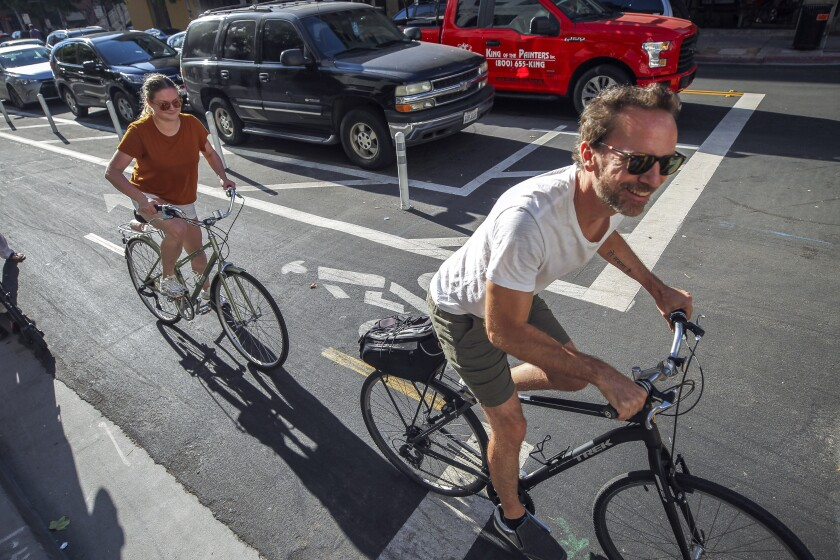 Dan Blanchett and his wife Goda Blanchett ride bicycles on a bike lane next to where cars park away from the curb in downtown San Diego in 2019.