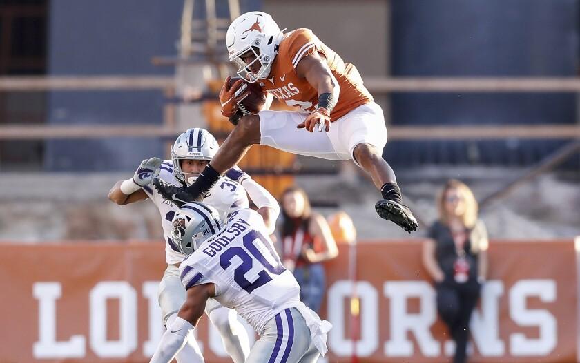 Texas quarterback Roschon Johnson hurdles Kansas State defensive back Denzel Goolsby.