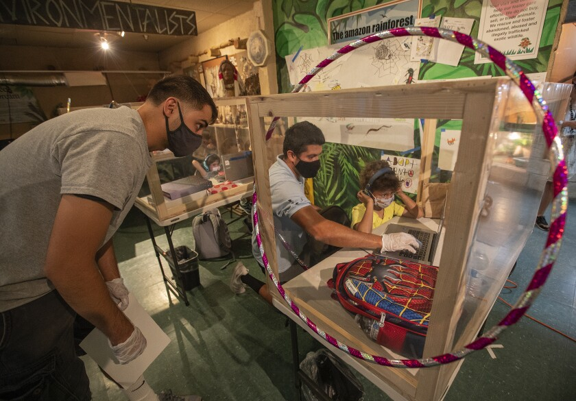 Kindergartner Jameson Miniex, 5, works with Kyle Fetter, left, and John Gaxiola inside his learning pod at Eco Station.