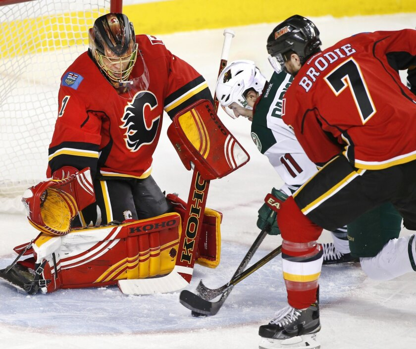 Minnesota Wild's Zach Parise (11) battles for the puck with Calgary Flames' TJ Brodie in front of Calgary goalie Jonas Hiller, from Switzerland, during the second period of an NHL hockey game Wednesday, Feb. 17, 2016, in Calgary, Alberta. (Larry MacDougal/The Canadian Press via AP)