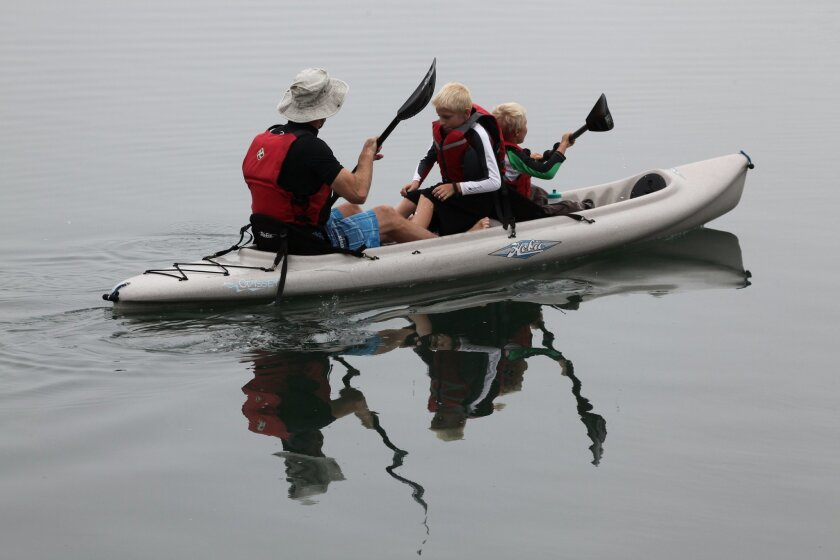 A family kayaks at Agua Hedionda Lagoon's Paddle Poker Challenge