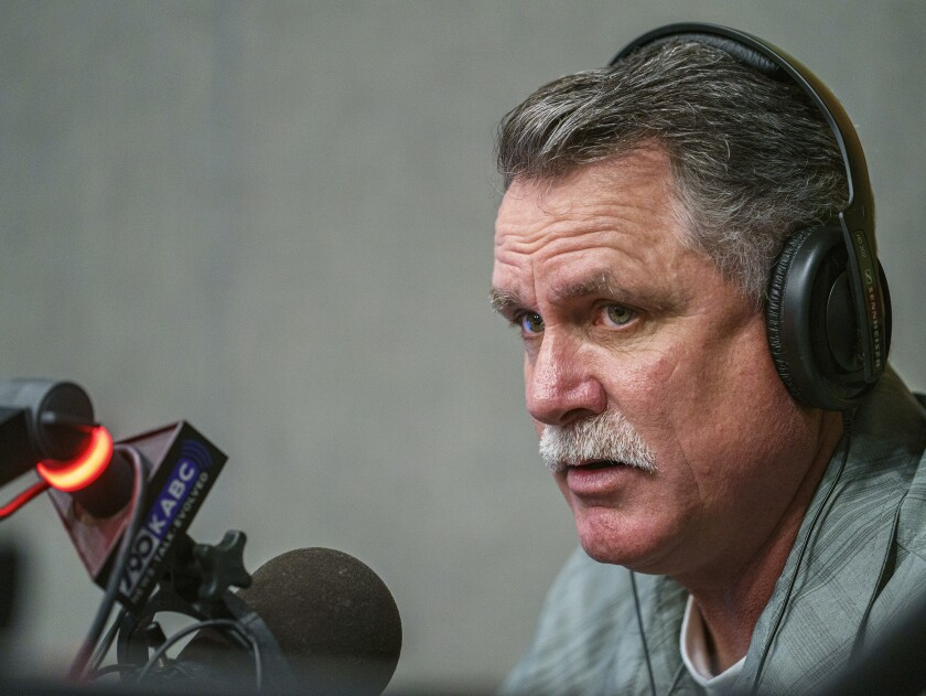A man with a mustache wears headphones in front of a radio microphone