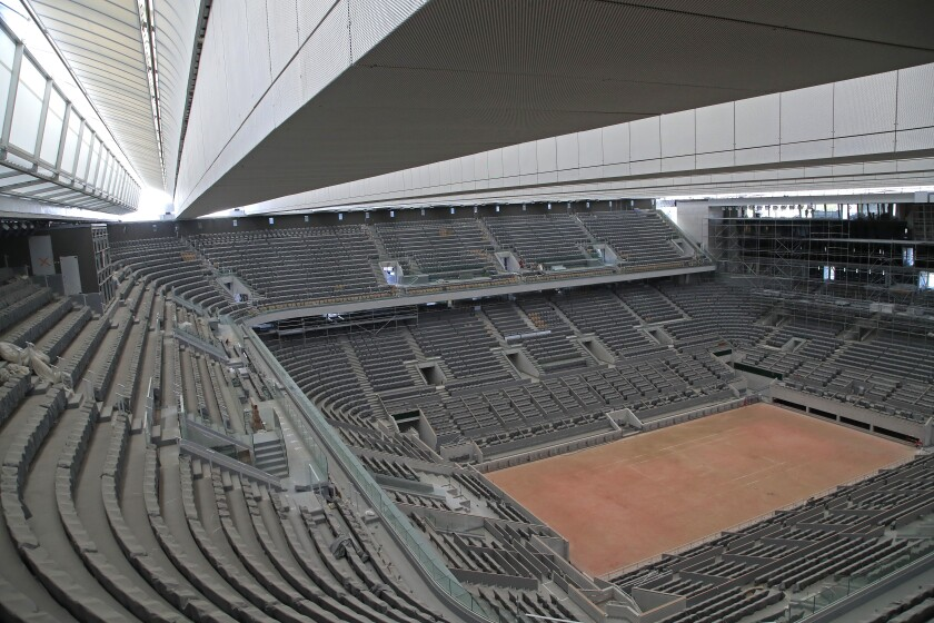 """FILE - In this Wednesday, May 27, 2020 file photo, a general view of the Philippe-Chatrier tennis court with its new retractable roof during a media tour at Roland Garros stadium in Paris. Damir Dzumhur's coach called Roland Garros organizers """"inhuman"""" on Tuesday, Sept. 22 for excluding the Bosnian player from the tournament, because the coach failed a coronavirus test. Dzumhur, a former top-30 player now ranked 114, tested negative for the virus himself but was barred from the qualifying draw for the clay major because he and his coach, Petar Popovic, shared a room in Paris. (AP Photo/Michel Euler, file)"""
