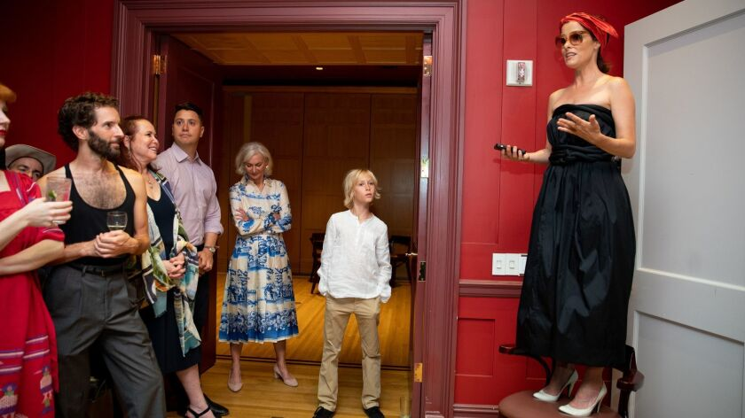 Parker Posey stands on a chair to talk at her book party hosted by Eileen Guggenheim at a private club in Manhattan.