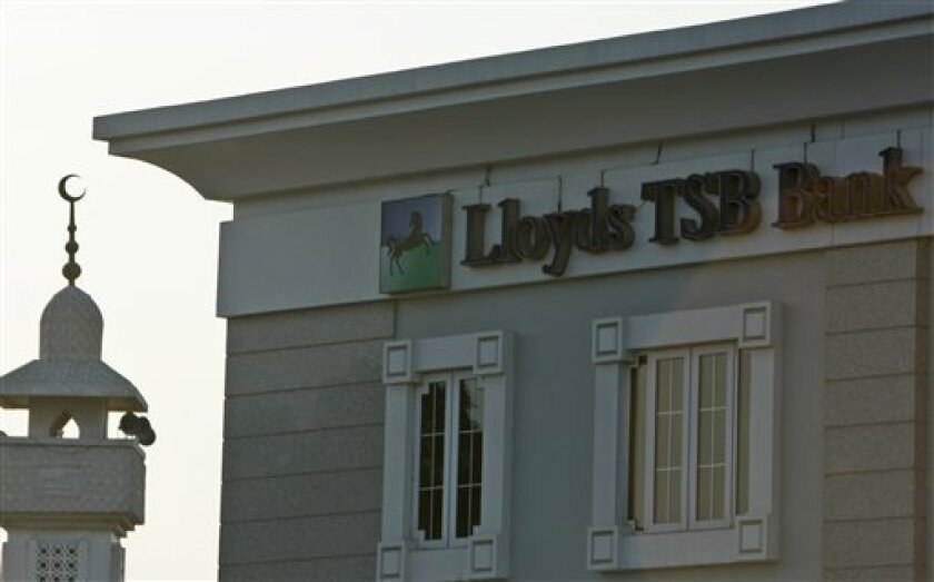 A minaret is seen behind a branch of Lloyds bank in Dubai, United Arab Emirates, Monday, Nov. 30, 2009. The heavily indebted Dubai World is not guaranteed by the emirate's government, a top financial official from the city state said Monday, offering little direction to anxious investors on a day w