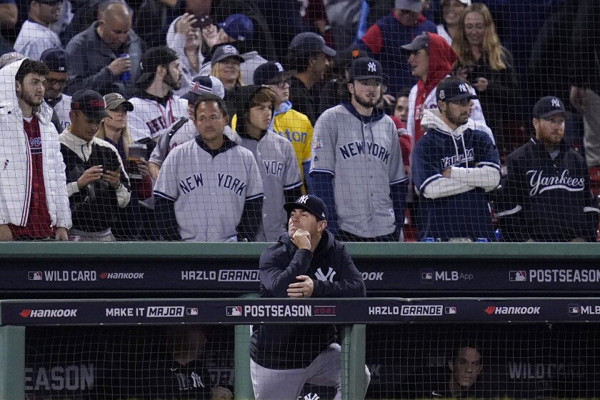 New York Yankees assistant hitting coach P.J. Pilittere lingers in the dugout after they were defeated by the Boston Red Sox 6-2 in an American League Wild Card playoff baseball game at Fenway Park, Tuesday, Oct. 5, 2021, in Boston. (AP Photo/Charles Krupa)
