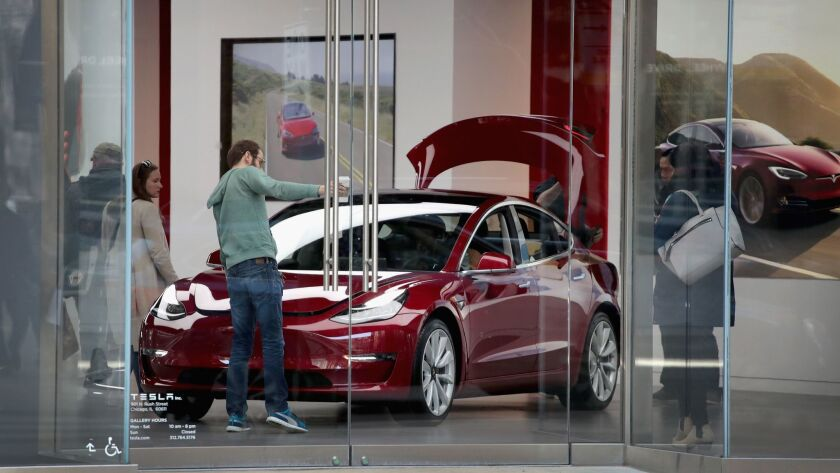 People look at a Tesla Model 3 sedan at a Tesla showroom in Chicago in March.