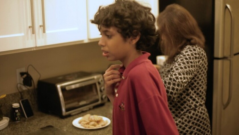 "Zain Hussain waiting for his mother, Mehreen, to prepare a meal for him in their Carlsbad kitchen in a scene from the movie ""Aging Out,"" about the challenging facing parents of aging children with autism."