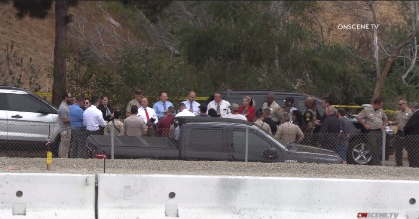Sheriff's homicide investigators huddle Friday morning in Encinitas after fatal shooting of a man by two deputies.