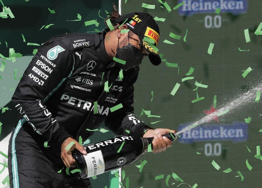 Mercedes driver Lewis Hamilton of Britain celebrates on the podium after winning the Portugal Formula One Grand Prix at the Algarve International Circuit near Portimao, Portugal, Sunday, May 2, 2021. (AP Photo/Manu Fernandez)
