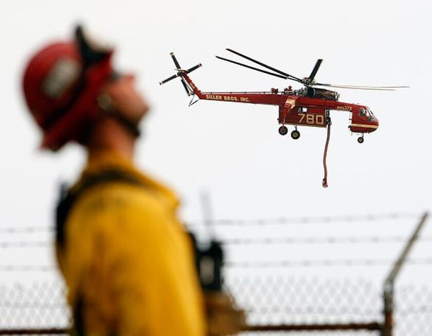 A water-dropping helicopter hovers near the southwestern flank of the Station fire, where California Office of Emergency Services firefighters monitor the progress.