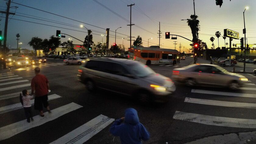 LOS ANGELES, CA - APRIL 14, 2015: Pedestrians cross with the light at the intersection of Slauson an