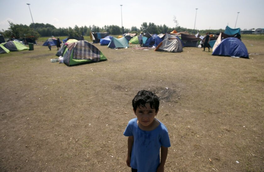 A boy stands in the makeshift refugee camp near the Horgos border crossing into Hungary, near Horgos, Serbia, Friday, May 27, 2016. Nearly 400,000 refugees passed through Hungary last year on their way to richer EU destinations. The flow was slowed greatly by Hungary's construction of razor-wire fe