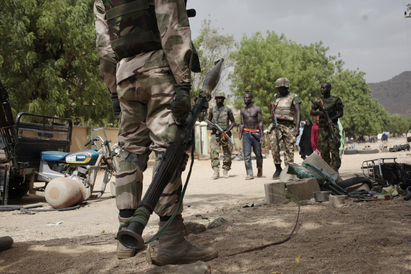 Nigerian soldiers in Gwoza escort Hassan Usman, who had been forced into labor by Boko Haram and had his hand amputated after the Islamic militants accused him of stealing fuel.