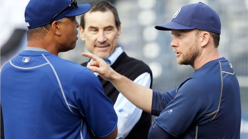 Padres manager Andy Green, right, talks with Los Angeles Dodgers manager Dave Roberts, left, in front of one of the Padres owners Peter Seidler, center, during warm ups before a baseball game between thePadres and the Los Angeles Dodgers in San Diego, Saturday, May 21, 2016.
