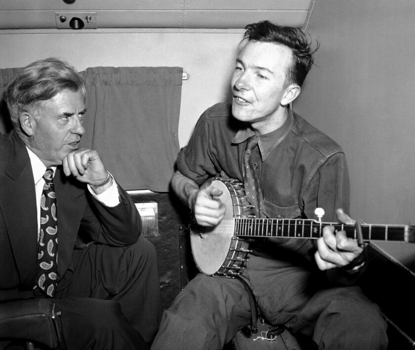 Henry A. Wallace, left, shown on a campaign flight in 1948, listens to Pete Seeger perform.