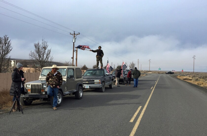 People wave American flags near the Malheur National Wildlife Refuge in Oregon as negotiations were underway that led to the surrender of the last four occupiers.