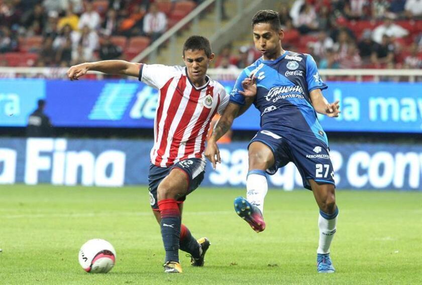 José Juan Macías (i) de Chivas disputa el balón contra Hugo Rodríguez (d) de Puebla en un partido de la jornada cinco del Torneo Apertura del fútbol mexicano en Guadalajara (México). EFE