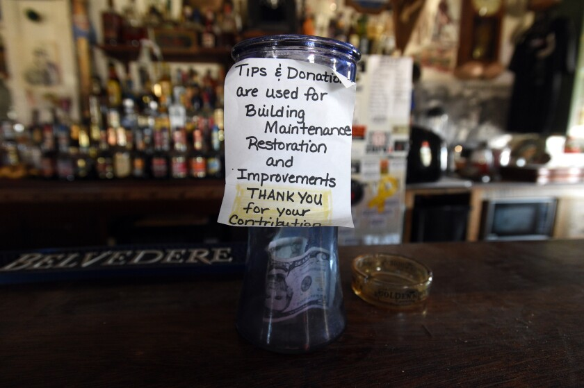 A donation cup sits on the bar top of Walt Kremin's Horn Silver Saloon in Gold Point, Nev. Without a liquor license to sell beer and other spirits, Kremin insists he only accepts donations as payment.