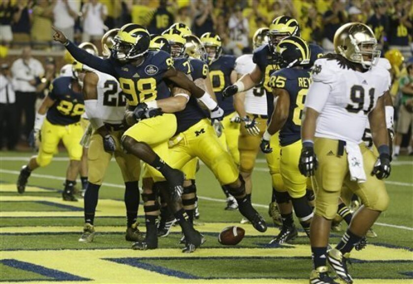 Michigan quarterback Devin Gardner (98) celebrates his touchdown during the second quarter of an NCAA college football game against Notre Dame in Ann Arbor, Mich., Saturday, Sept. 7, 2013. (AP Photo/Carlos Osorio)