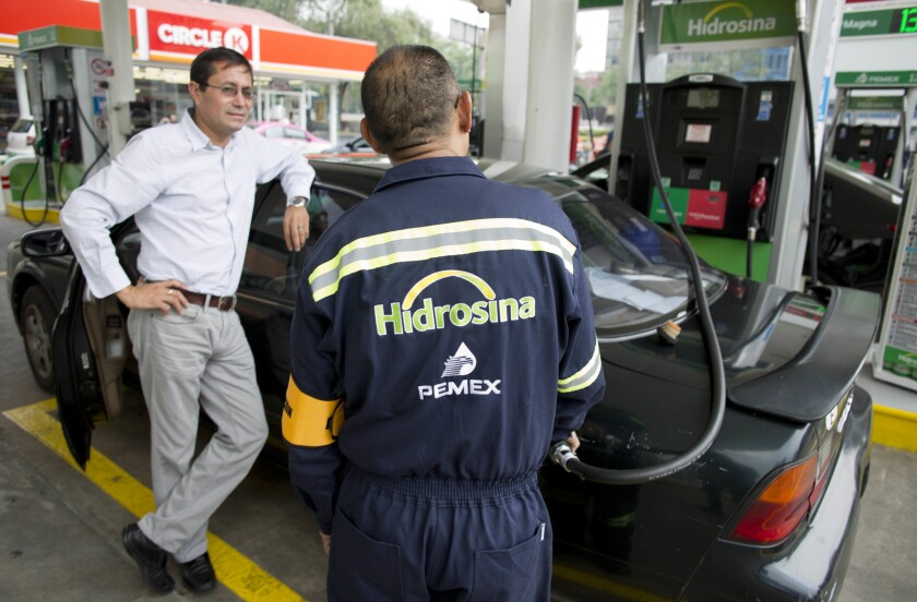 Un empleado de Hidrosina carga gasolina para un cliente en Ciudad de México. Por primera vez en casi ocho décadas, las gasolineras Pemex tienen competencia en las calles y carreteras de México. Dos compañías han inaugurado tres gasolineras bajo sus propias marcas, lo que acabó con uno de los últimos monopolios que le quedaban a la petrolera estatal. (AP Foto/Eduardo Verdugo)