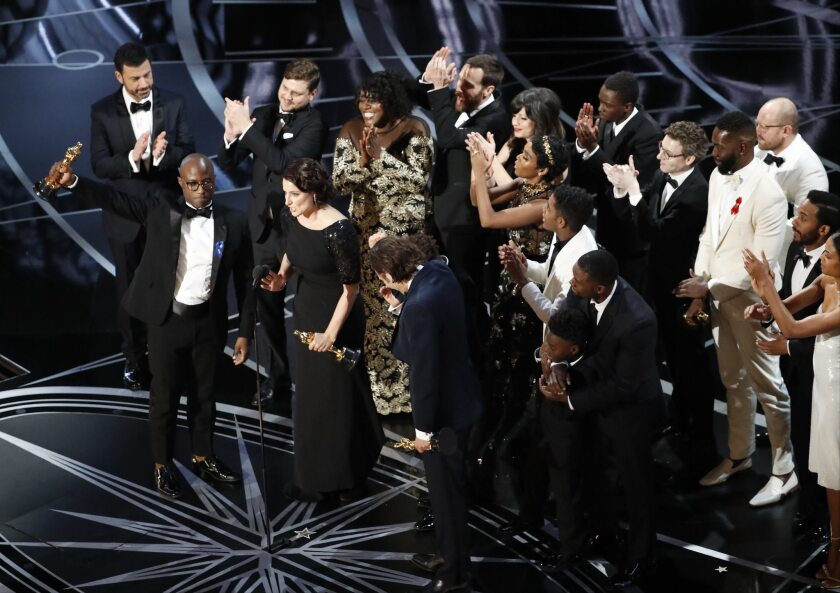 """Barry Jenkins holds up a best picture Oscar for """"Moonlight."""""""