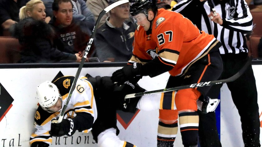 Ducks forward Nick Ritchie checks Bruins defenseman Colin Miller during the first period of a game Wednesday night at Honda Center. The Ducks won, 5-3.